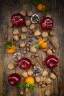 Rote Äpfel, Mandarinen, Haselnüsse, Walnüsse, Zimtstangen und Tannenzapfen auf dunklem Holz — Stockfoto