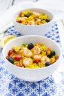 Paella mit Reis, Paprika, Tomate, Artischocke, Erbse, schwarzer Olive, Kurkuma und Garnelen — Stockfoto