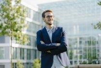 Jovem empresário em pé em frente ao edifício de escritórios moderno, com braços cruzados — Fotografia de Stock