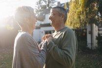 Счастливая любящая старшая пара в саду — стоковое фото
