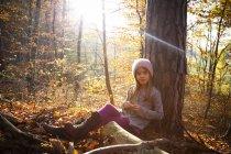 Jovem sentada na árvore no outono — Fotografia de Stock