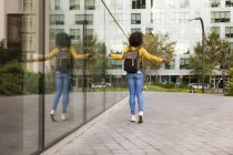 Back view of woman with backpack walking in the city — Stockfoto