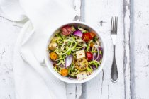 Bowl of zoodles with fried tofu, red quinoa, red onions and tomatoes — стоковое фото
