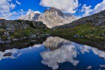 Italy, Veneto, Dolomites, Fiemme Mountains, Cimon della Pala, reflected in a small lake — Stock Photo