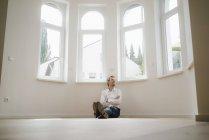 Uomo d'affari seduto a terra della sua casa appena ristrutturata, cercando felice — Foto stock