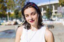 Портрет улыбающейся молодой женщины с наушниками в городе — стоковое фото