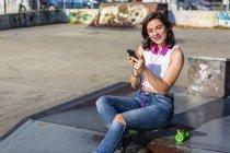 Retrato de jovem sorridente com fones de ouvido e telefone celular em um parque de skate — Fotografia de Stock