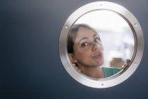 Портрет женщины, выглядывающей из-за иллюминатора — стоковое фото