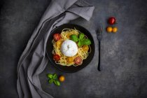 Spaghetti with tomatoes, burrata and basil leaves, from above — Stock Photo