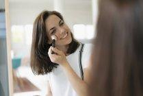 Красивая женщина наносит макияж, используя тушь — стоковое фото