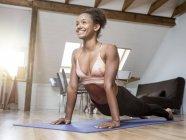 Улыбающаяся молодая женщина практикующая йогу — стоковое фото