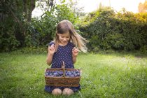 Smiling girl crouching on a meadow with wickerbasket of plums — Stock Photo