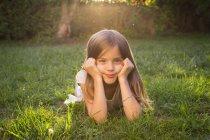 Porträt eines kleinen Mädchens, das in der Abenddämmerung auf einer Wiese liegt — Stockfoto