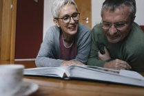 Senior couple lying on the floor at home looking at photo album — Stock Photo