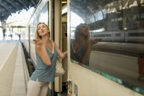 Young woman entering a train at the train station blowing a kiss — Stock Photo