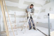 Portrait of happy father and son working on loft conversion — Stock Photo