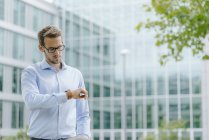 Young businessman standing in front of modern office building, checking the time — Stock Photo