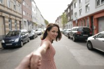 Woman walking in street, holding hand of a man — Stock Photo