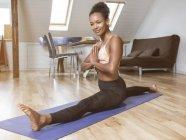 Retrato de sorrir jovem mulher no ioga pose fazendo divisões — Fotografia de Stock