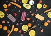 Three various sugar-free popsicles, fruits and vegetables on black wood — Stock Photo