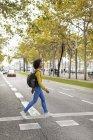 Frau überquert mit Rucksack die Straße — Stockfoto