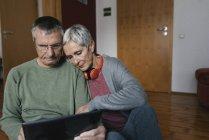 Старшая пара сидит на полу дома и смотрит на планшет — стоковое фото