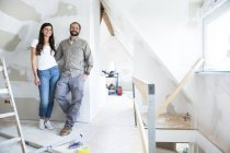 Portrait of confident couple standing in attic to be renovated — Stock Photo