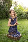 Portrait of smiling girl on a meadow with wickerbasket of plums — Stock Photo
