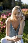 Smiling young woman sitting in park with cell phone and earbuds — Stock Photo