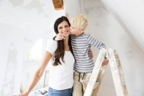Portrait of happy mother and son working on loft conversion — Stock Photo