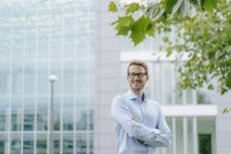 Young businessman standing in front of modern office building, with arms crossed — Stock Photo