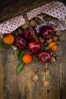Cesto di vimini, mele rosse, mandarini, nocciole e noci su legno scuro — Foto stock