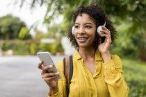 Ritratto di donna sorridente che ascolta musica con cuffie e smartphone all'aperto — Foto stock