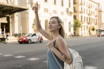 Smiling young woman in the city hailing a taxi — Stock Photo