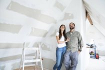 Confident couple standing in attic to be renovated looking up — Stock Photo