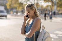 Молодая женщина разговаривает по мобильному телефону в городе — стоковое фото