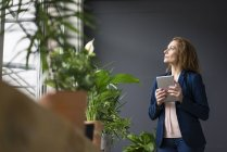 Mature businesswoman working in sustainable office, using digital tablet — Stock Photo