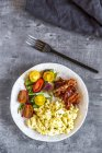 Scrambled eggs with fried bacon and salad with tomato, low carb, from above — Stock Photo