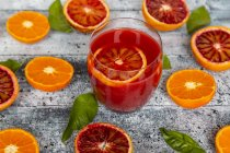 Glass of blood orange juice and halves of blood oranges and tangerines — Stock Photo