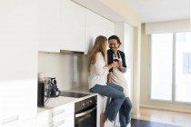 Ласковая пара, пьющая красное вино на кухне — стоковое фото