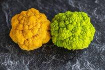 Coliflor amarilla y verde brillante en pizarra - foto de stock
