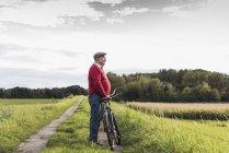 Homem idoso com bicicleta na paisagem rural — Fotografia de Stock