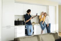 Друзья веселятся, стоя на кухне, фотографируя со своими смартфонами — стоковое фото