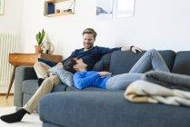 Glückliches Paar entspannt auf der Lounge-Couch in ihrem modernen Wohnzimmer — Stockfoto