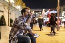Regno Unito, Londra, uomo seduto su una panchina di notte a bere dalla tazza — Foto stock
