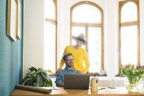 Случайная предпринимательская пара в домашнем офисе работает за ноутбуком и улыбается — стоковое фото