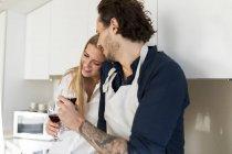 Affettuosa coppia che beve vino rosso in cucina — Foto stock