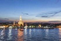 Tailandia, Bangkok, templo de Wat Arun al atardecer con el río Chao Phraya en primer plano - foto de stock