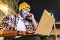 Regno Unito, Londra, uomo sorridente che usa telefono e laptop in città di notte — Foto stock