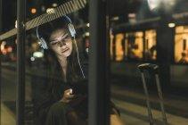 Portrait de jeune femme avec écouteurs attendant à la gare la nuit à l'aide d'une tablette — Photo de stock